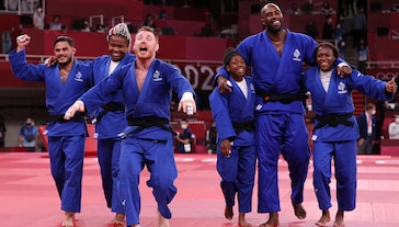 Team France celebrate victory over Team Japan during the Mixed Team Final