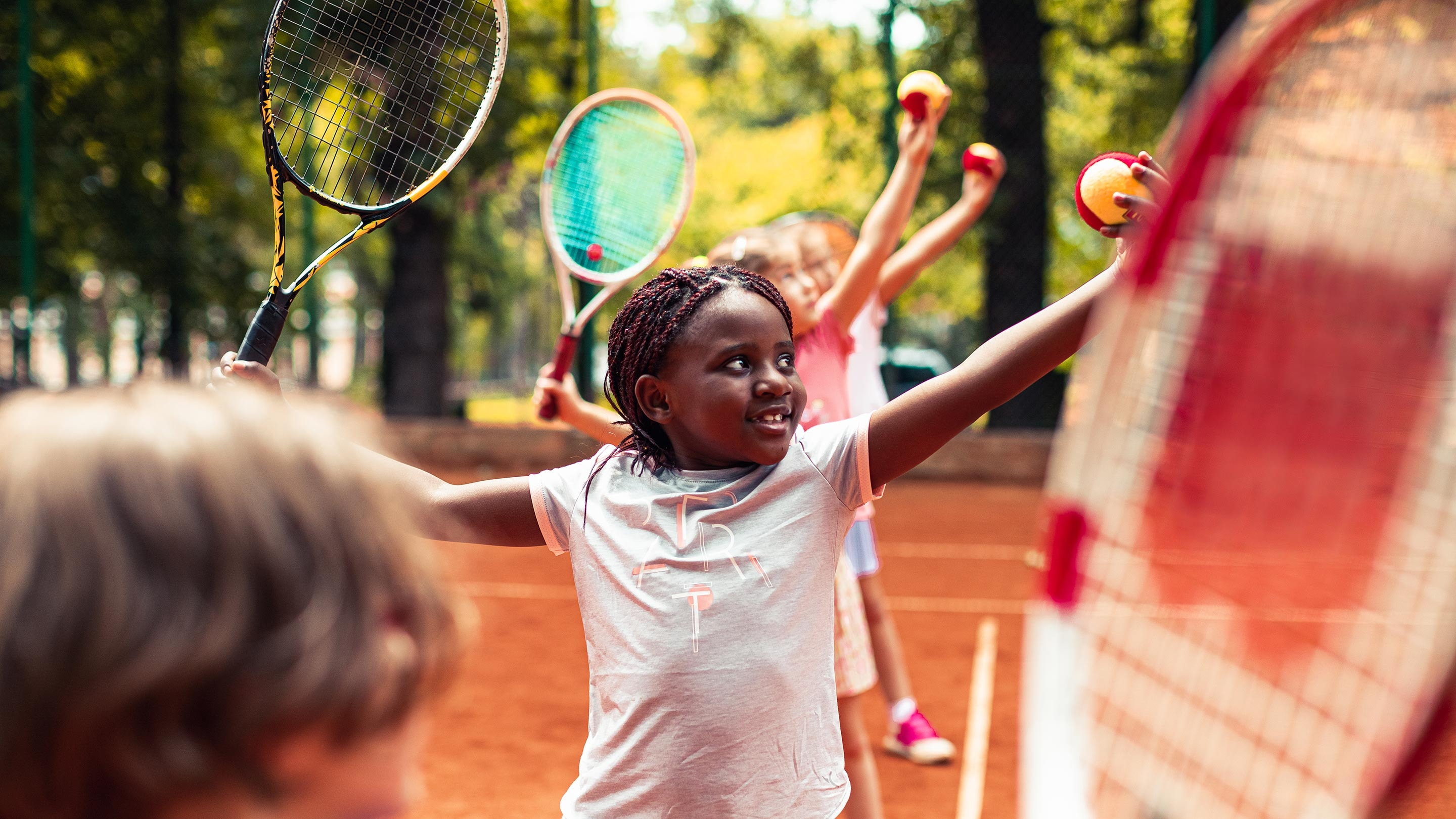 Close up of a group of kids on a tennis court learning how to serve
