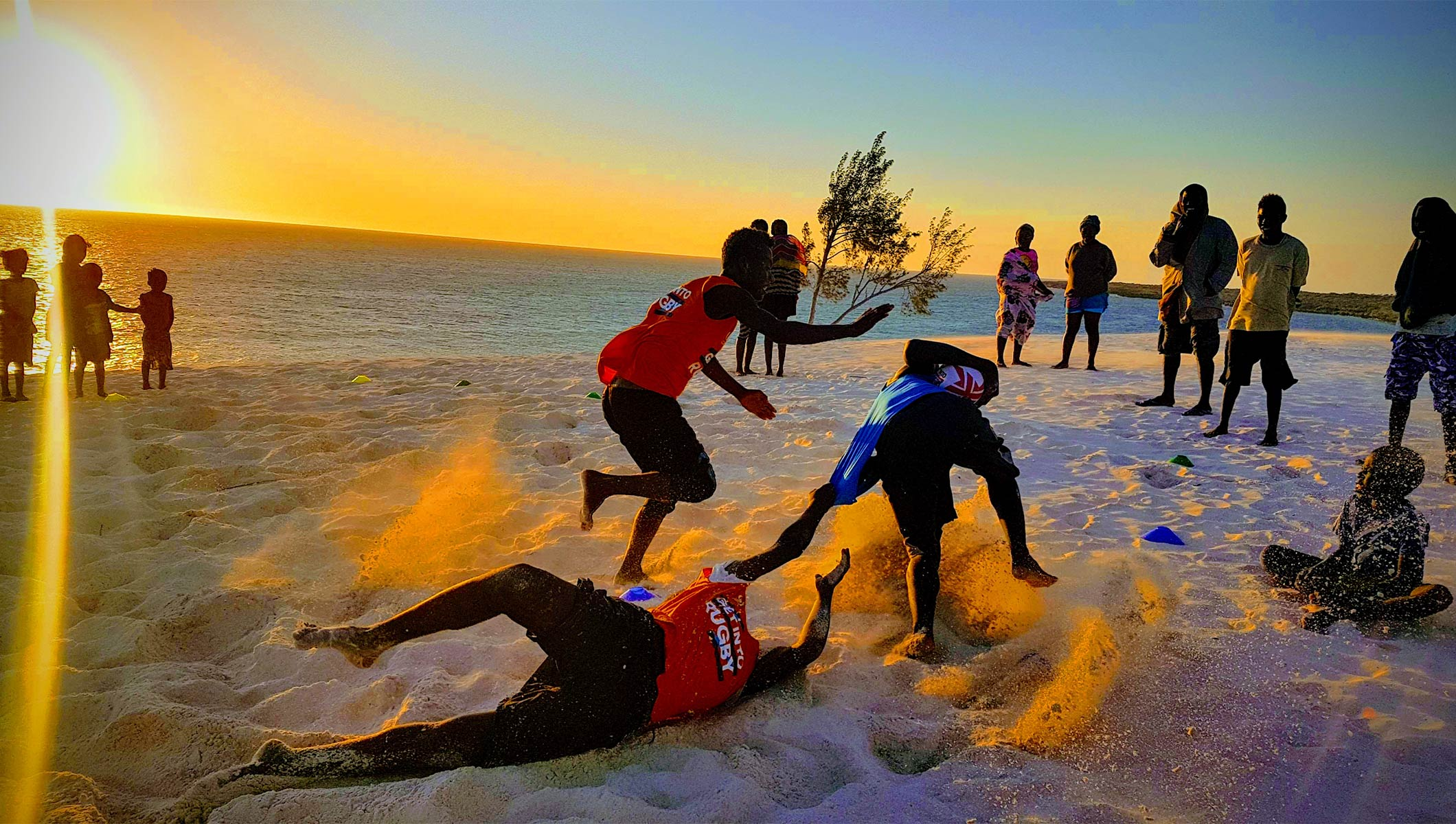 TERRES EN MÊLÉES - young people playing rugby on the beach
